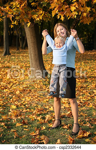 mother holds son for the hands in the park in autumn - csp2332644