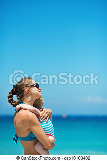 Mother hugging baby on beach - csp10103402