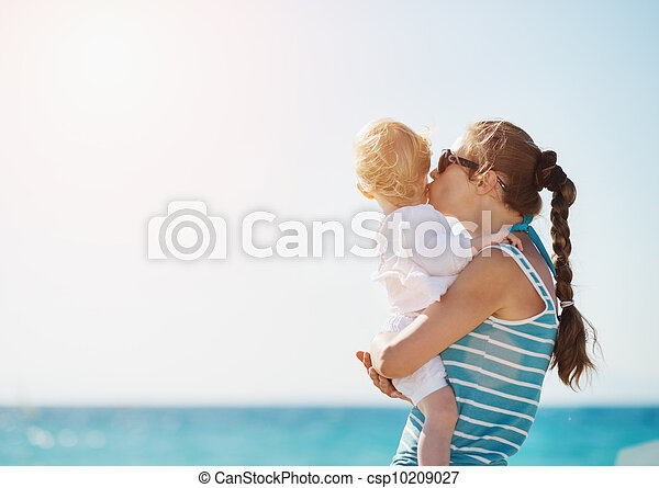 Mother kissing baby on beach - csp10209027