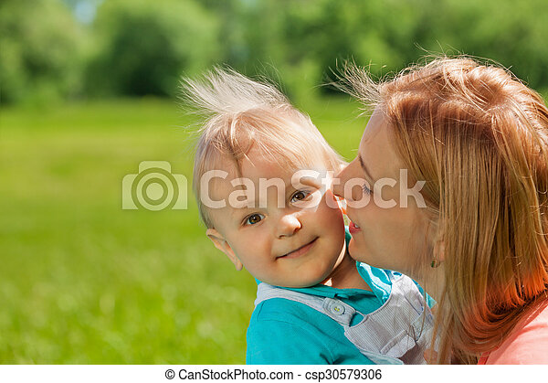 Mother kissing her child in cheek during summer - csp30579306