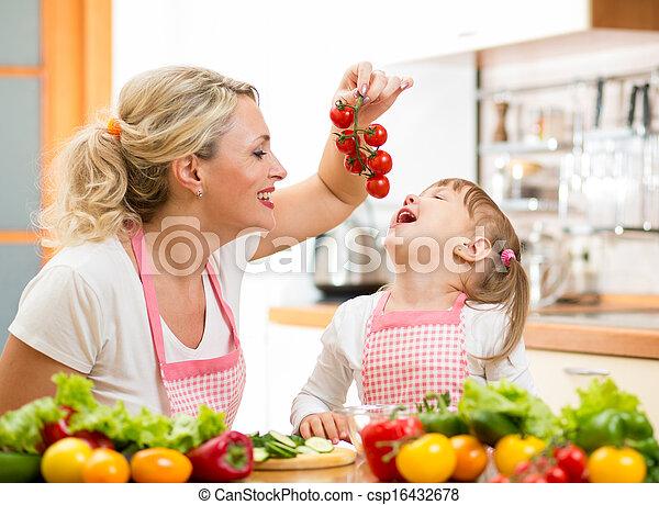 mother preparing dinner and feeding kid  tomato in kitchen  - csp16432678