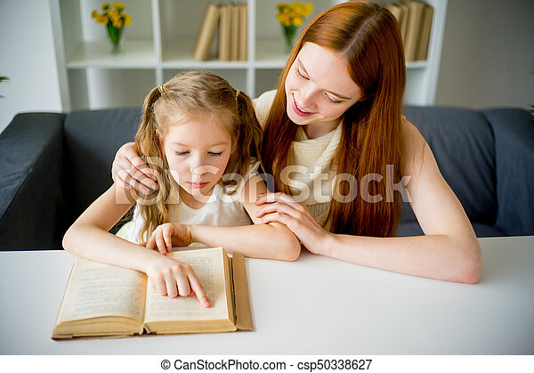 Mother reading a book to her daughter - csp50338627