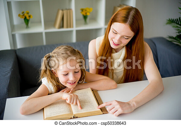 Mother reading a book to her daughter - csp50338643