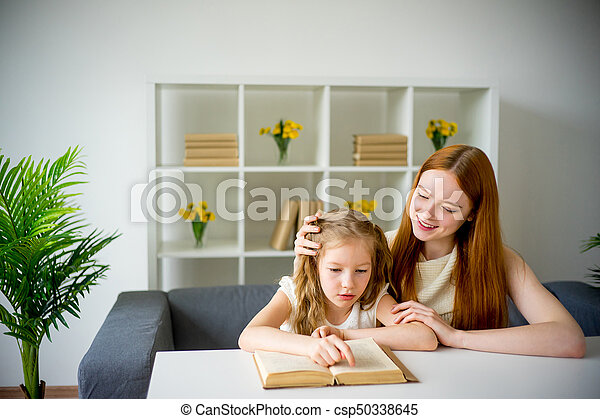 Mother reading a book to her daughter - csp50338645