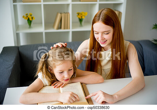 Mother reading a book to her daughter - csp50338630