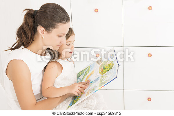Mother reading a book to her kid - csp34569312
