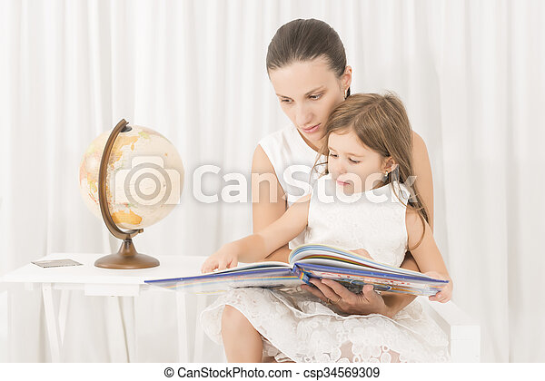 Mother reading a book to her kid - csp34569309