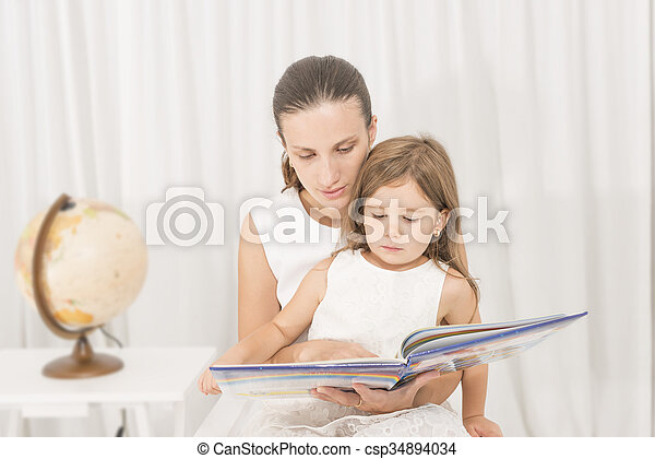 Mother reading a book to her kid - csp34894034