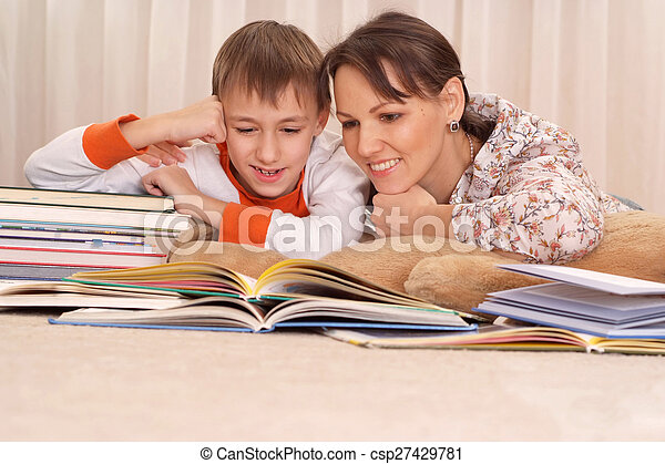 mother reading a book to kid boy  - csp27429781