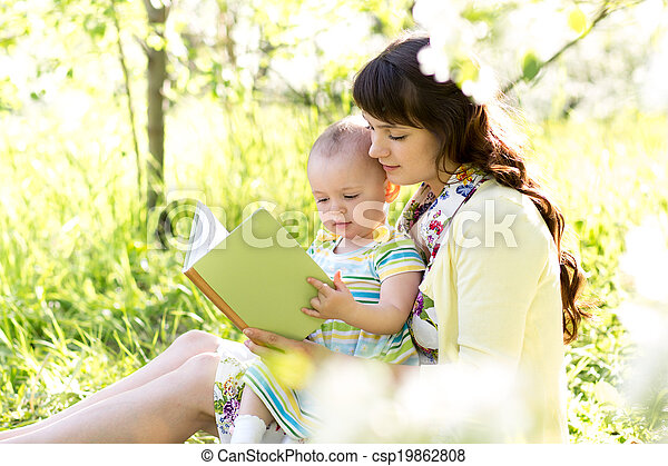 mother reading a book to kid outdoors - csp19862808