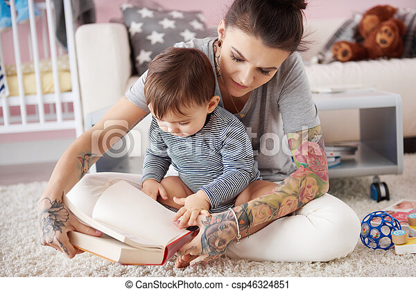 Mother reading book to her son - csp46324851