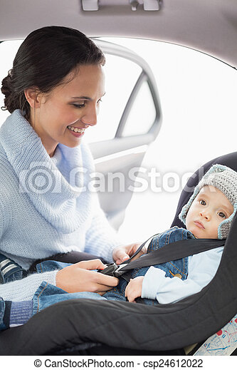 Mother securing her baby in the car seat - csp24612022
