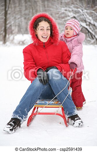 mother sits on sled in park with child at winter - csp2591439