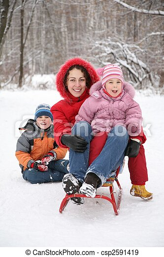 mother sits on sled with children in park at winter - csp2591419