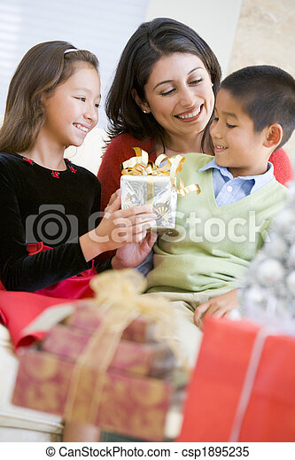 Mother Sitting With Her Son And Daughter,Exchanging Christmas Gi - csp1895235