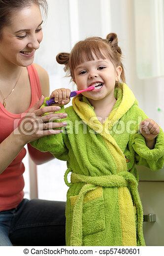 mother teaching daughter child teeth brushing in bathroom - csp57480601