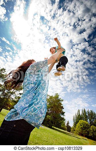 Mother Throwing Daughter in Air - csp10813329