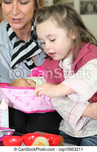 Mother watching little girl play with toy doll - csp10953211