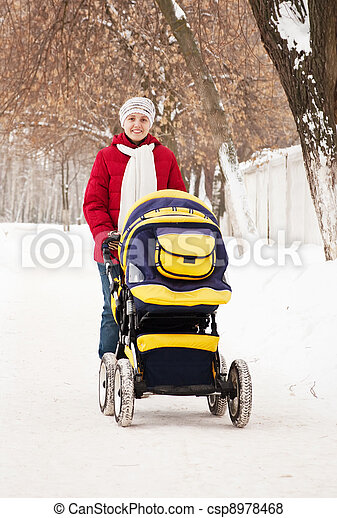 mother with carriage in winter park - csp8978468