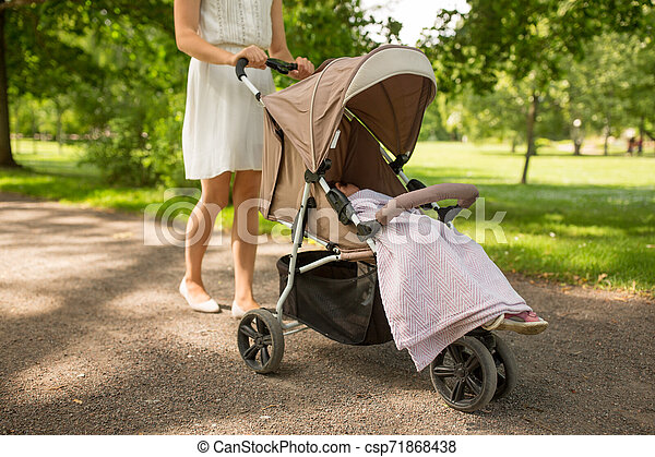 mother with child in stroller walking at park - csp71868438