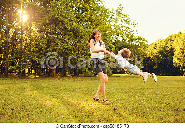 Mother with child playing in the park at sunset. - csp58185173