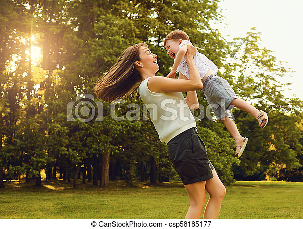 Mother with child playing in the park at sunset. - csp58185177