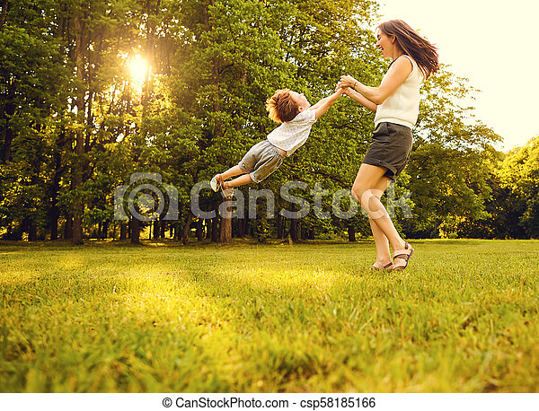 Mother with child playing in the park at sunset. - csp58185166