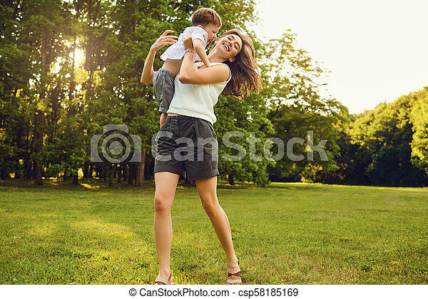 Mother with child playing in the park at sunset. - csp58185169
