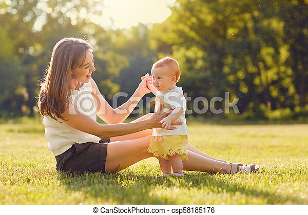 Mother with child playing on grass at sunset. - csp58185176