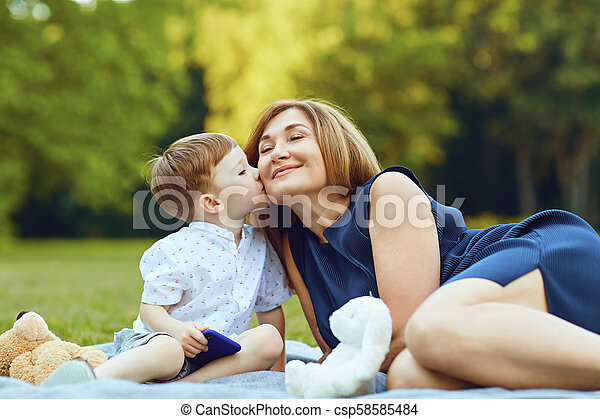 Mother with child playing on grass at sunset in summer - csp58585484