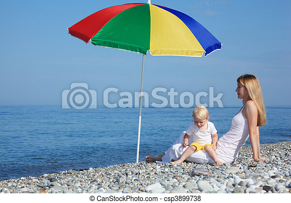 Mother with child under a multi colored umbrella on pebble beach - csp3899738
