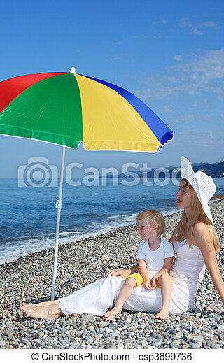 Mother with child under a multi colored umbrella on pebble beach - csp3899736