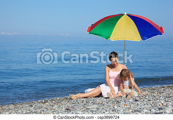 Mother with child under a multi colored umbrella on pebble beach - csp3899724