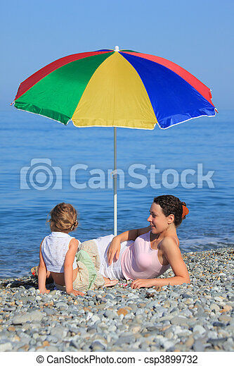 Mother with child under a multi colored umbrella on pebble beach - csp3899732