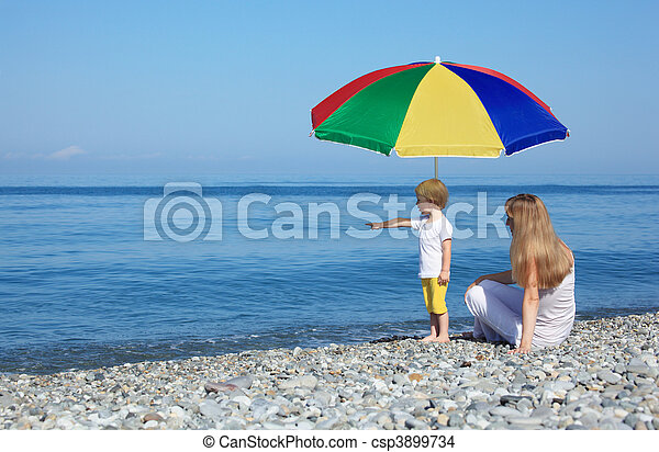 Mother with child under a multi colored umbrella on pebble beach - csp3899734