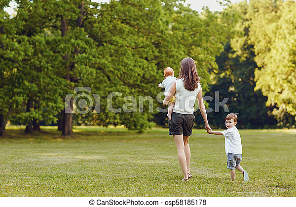 Mother with children in summer park. - csp58185178