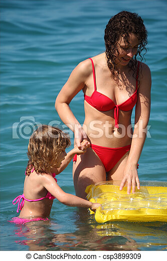 Mother with daughter in sea with inflatable mattress - csp3899309