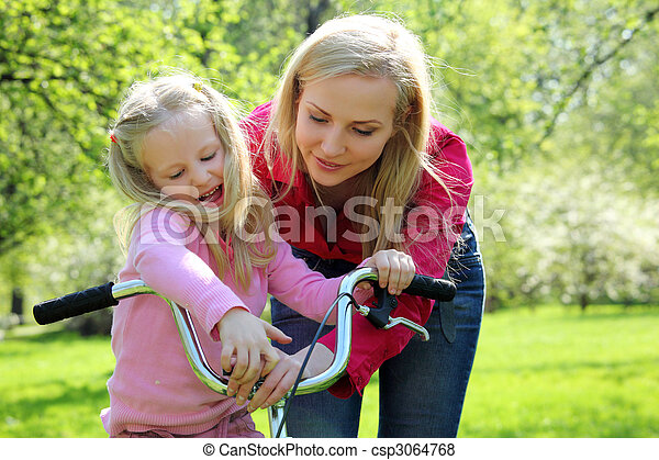 Mother with  daughter on bicycle in spring garden - csp3064768