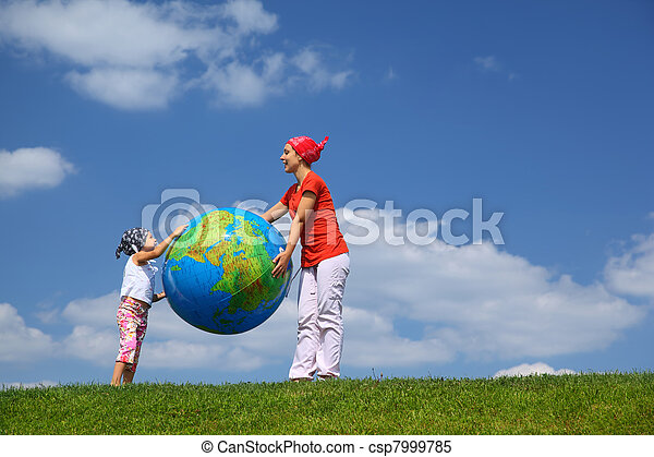 Mother with daughter stand on  grass and hold  large inflatable ball as  globe - csp7999785