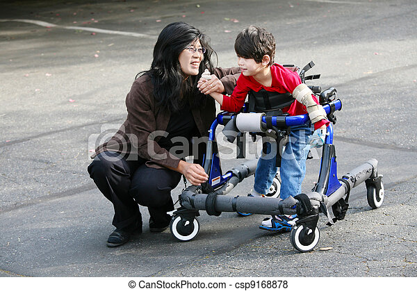 Mother with disabled son walking outdoors with walker, medical mobility equipment - csp9168878