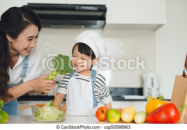 Mother with her daughter in the kitchen cooking together - csp50598963