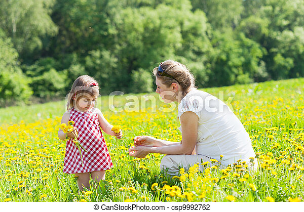 Mother with the small daughter play on a glade with dandelions - csp9992762