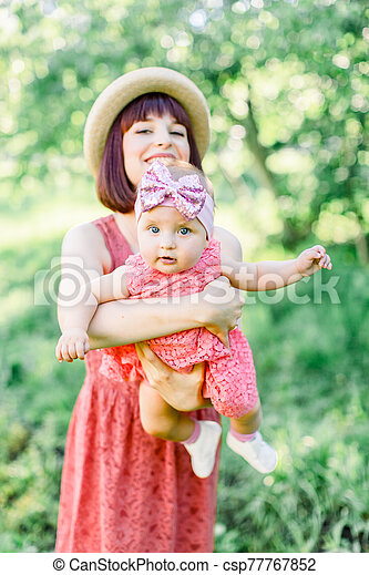 Mother with the straw hat And her little daughter outdoors family look in in a pink dress . Outdoor Portrait of happy family. family look. Happy mother having fun with her daughter - csp77767852