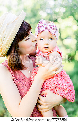 Mother with the straw hat And her little daughter outdoors family look in in a pink dress . Outdoor Portrait of happy family. family look. mom kisses daughter in a cheek. - csp77767854