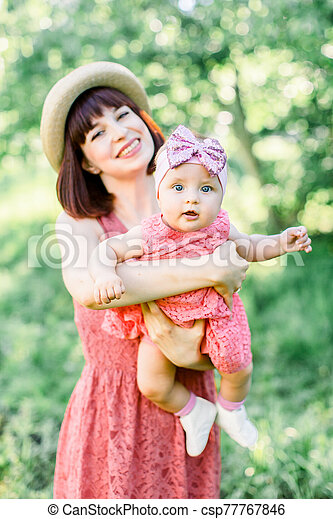 Mother with the straw hat And her little daughter outdoors family look in in a pink dress . Outdoor Portrait of happy family. family look. Happy mother having fun with her daughter - csp77767846