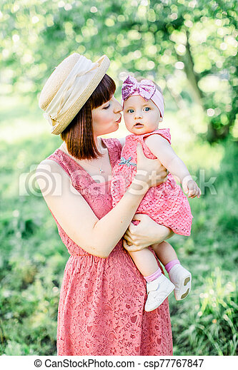 Mother with the straw hat And her little daughter outdoors family look in in a pink dress . Outdoor Portrait of happy family. family look. mom kisses daughter in a cheek. - csp77767847
