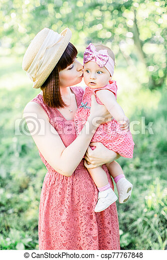 Mother with the straw hat And her little daughter outdoors family look in in a pink dress . Outdoor Portrait of happy family. family look. mom kisses daughter in a cheek. - csp77767848
