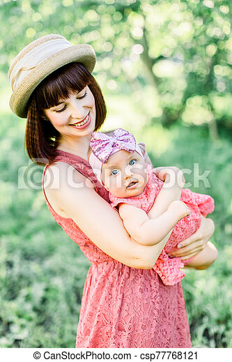 Mother with the straw hat And her little daughter outdoors family look in in a pink dress . family look. Young mother throws up baby in the sky, on sunny day. - csp77768121