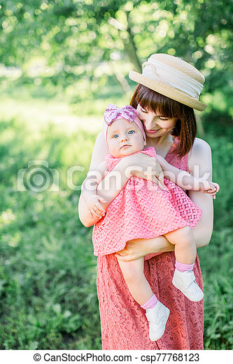 Mother with the straw hat And her little daughter outdoors family look in in a pink dress . Young mother with her little baby on the meadow - csp77768123