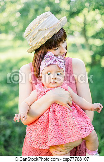Mother with the straw hat And her little daughter outdoors family look in in a pink dress . Outdoor Portrait of happy family. family look. Positive human emotions, feelings, emotions. - csp77768107